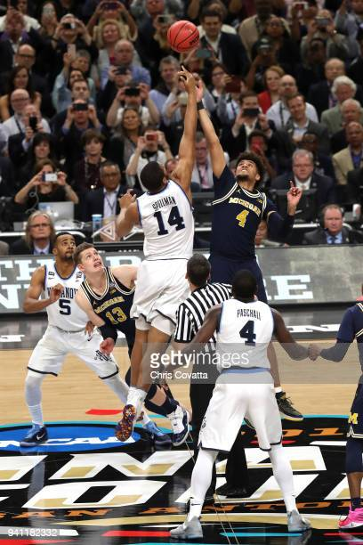 Omari Spellman of the Villanova Wildcats and Isaiah Livers of the Michigan Wolverines go up for the opening tip during the 2018 NCAA Men's Final Four...