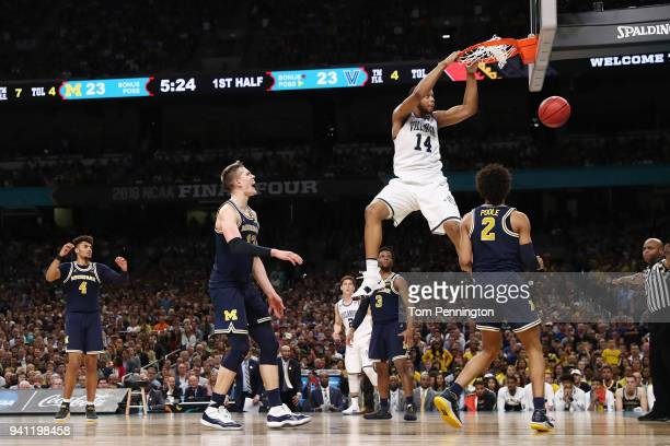 Omari Spellman of the Villanova Wildcats dunks in the first half against Jordan Poole of the Michigan Wolverines during the 2018 NCAA Men's Final...