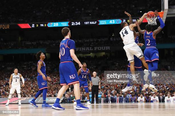 Omari Spellman of the Villanova Wildcats goes up for a dunk against Silvio De Sousa and Lagerald Vick of the Kansas Jayhawks in the first half during...