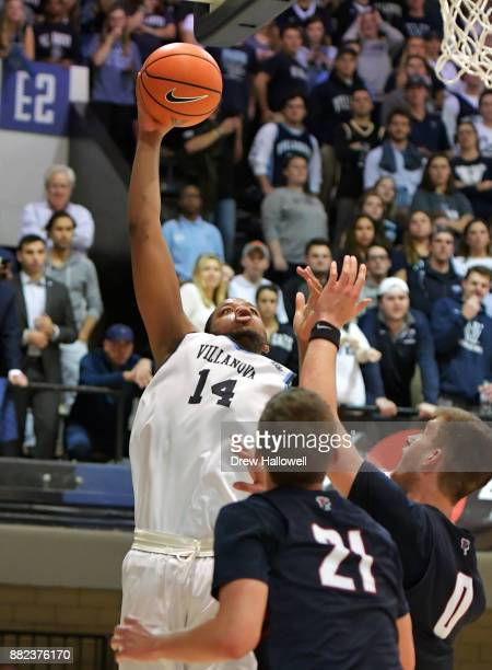 Omari Spellman of the Villanova Wildcats puts up a shot over Ryan Betley and Max Rothschild of the Pennsylvania Quakers at Jake Nevin Field House on...