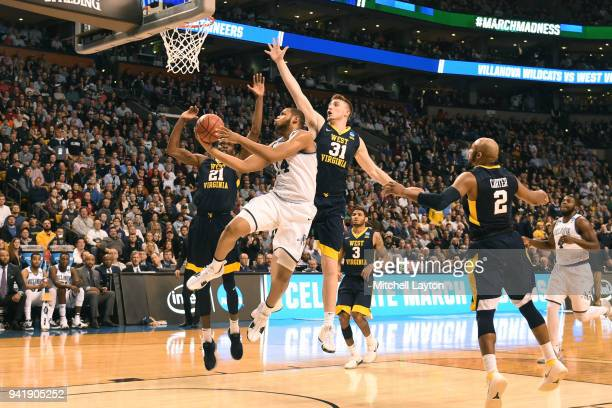 Omari Spellman of the Villanova Wildcats tdrives to the basket by Logan Routt of the West Virginia Mountaineers during the 2018 NCAA Men's Basketball...