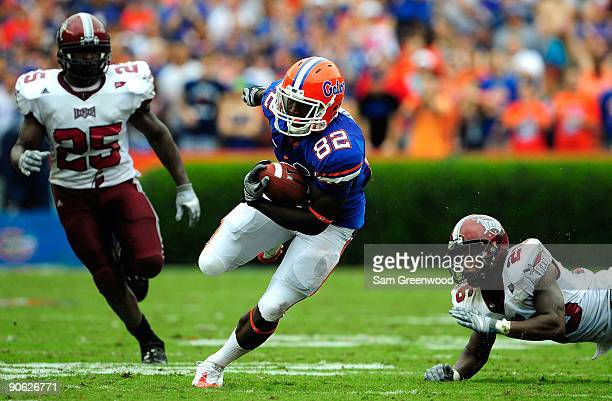 Omarius Hines of the Florida Gators runs past Bryan Willis and Xavier Lamb of the Troy Trojans during game at Ben Hill Griffin Stadium on September...