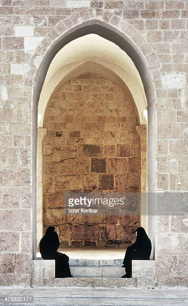 omayyad mosque two women sitting under one arch - syria stock pictures, royalty-free photos & images