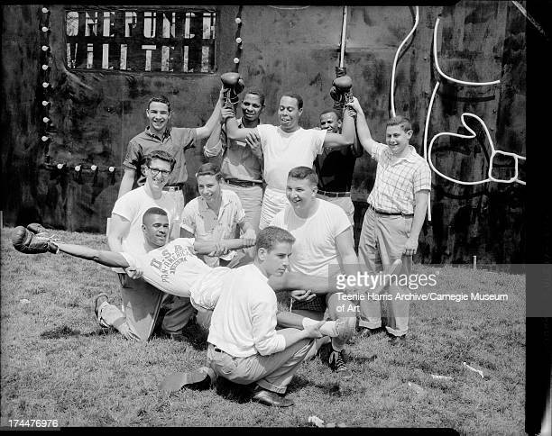 Omega Psi Phi and Kappa Nu fraternity members including Arnold 'Arnie' Sowell lying down and Joe Sanford with boxing gloves raised posed outdoors in...