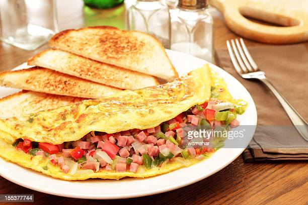 Omelet and white toast on a plate on a wooden table
