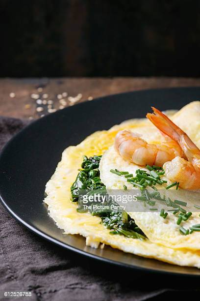 Omelet with cooked spinach and fried shrimps prawns, served with cutting chive and sesame seeds