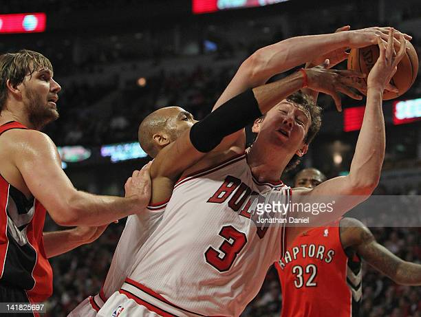 Omer Asik and Taj Gibson of the Chicago Bulls battle for a rebound next to Aaron Gray of the Toronto Raptors at the United Center on March 24 2012 in...