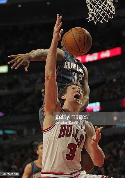 Omer Asik of the Chicago Bulls is fouled while shooting by Boris Diaw of the Charlotte Bobcats at the United Center on January 21 2012 in Chicago...
