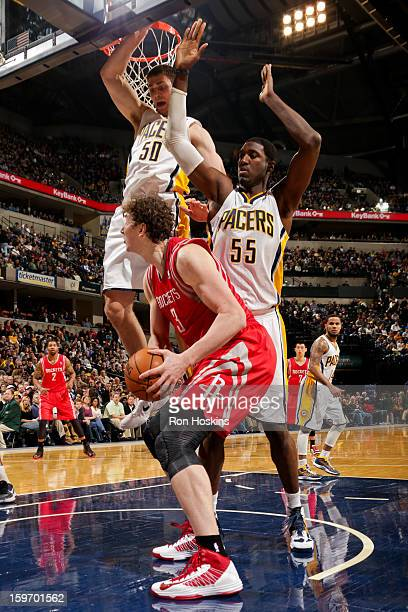 Omer Asik of the Houston Rockets drives to the basket against Tyler Hansbrough and Roy Hibbert of the Indiana Pacers of the Indiana Pacers of the...