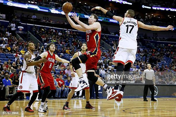 Omer Asik of the New Orleans Pelicans drives to the basket past Jonas Valanciunas of the Toronto Raptors during the first half of a game at the...