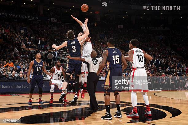 Omer Asik of the New Orleans Pelicans goes up for the opening tip off against Jonas Valanciunas of the Toronto Raptors on November 13 2015 at the Air...