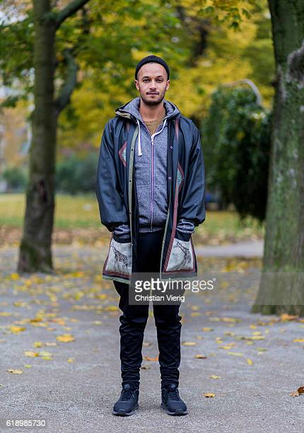 Omer Eltigani wearing a grey rain coat with prints a black sailor wool hat a grey hoody with zipper black cotton pants black Nike sneaker on October...