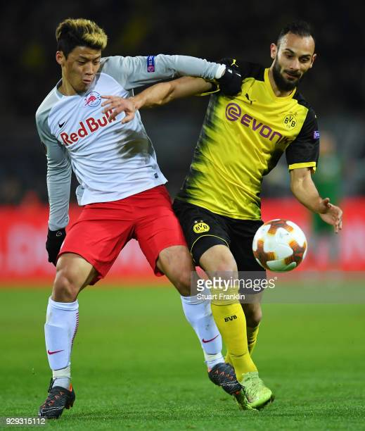 Omer Toprak of Borussia Dortmund and Hwang HeeChan of Red Bull Salzburg battle for the ball during the UEFA Europa League Round of 16 match between...