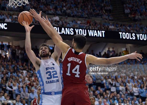 Omer Yurtseven of the North Carolina State Wolfpack defends a shot by Luke Maye of the North Carolina Tar Heels during their game at the Dean Smith...