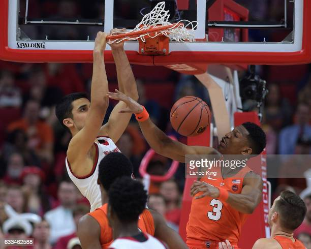 Omer Yurtseven of the North Carolina State Wolfpack dunks the ball against Andrew White III of the Syracuse Orange at PNC Arena on February 1, 2017...