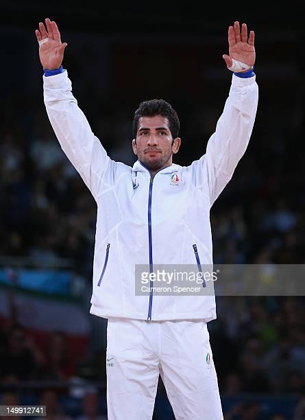 Omid Haji Noroozi of Islamic Republic of Iran celebrates on the podium after beating Revaz Lashkhi of Georgia in their Men's GrecoRoman 60 kg Gold...