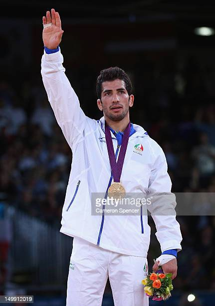 Omid Haji Noroozi of Islamic Republic of Iran celebrates on the podium with his Gold medal after beating Revaz Lashkhi of Georgia in their Men's...