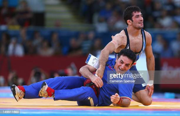 Omid Haji Noroozi of Islamic Republic of Iran celebrates with his Coach after beating Revaz Lashkhi of Georgia in their Men's Greco-Roman 60 kg Gold...