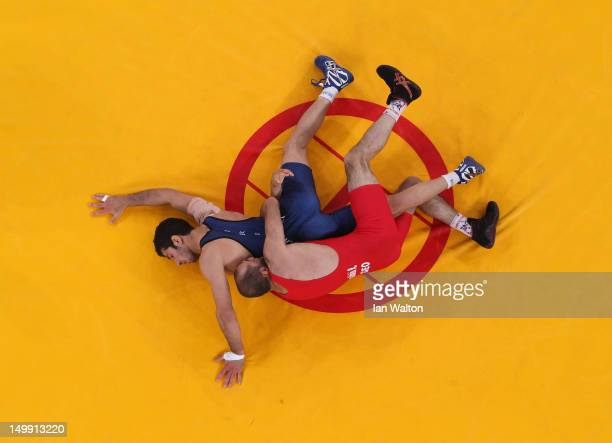 Omid Haji Noroozi of Islamic Republic of Iran competes with Revaz Lashkhi of Georgia in their Men's GrecoRoman 60 kg Gold Medal bout on Day 10 of the...