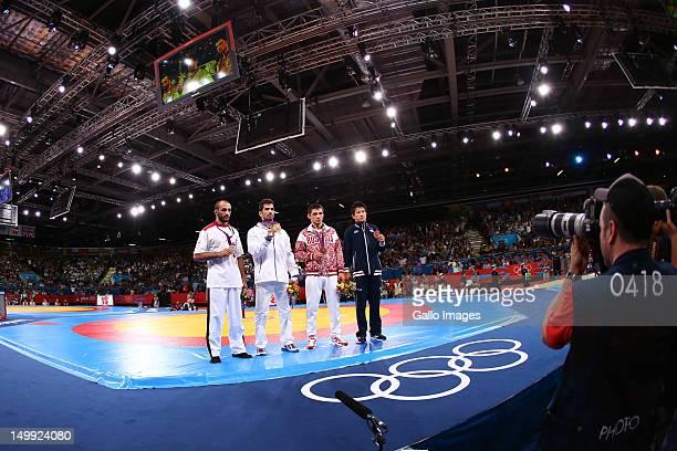 Omid Haji Noroozi of Islamic Republic of Iran stands on the podium with his Gold medal, Revaz Lashkhi of Georgia the Silver and Zaur Kuramagomedov of...