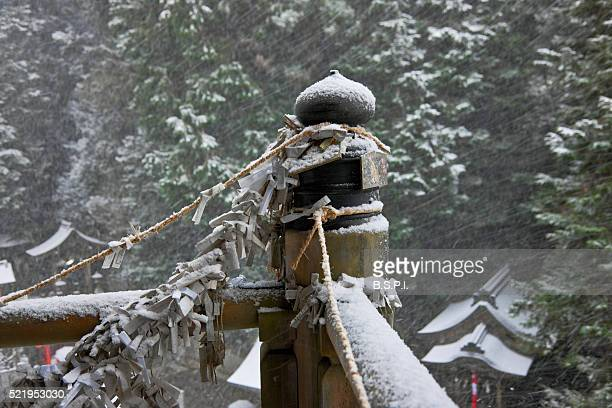 o-mikuji fortunes tied to honden hall railing at snowy tanukidani fudo-in temple in kyoto, japan - shingon buddhismus stock-fotos und bilder