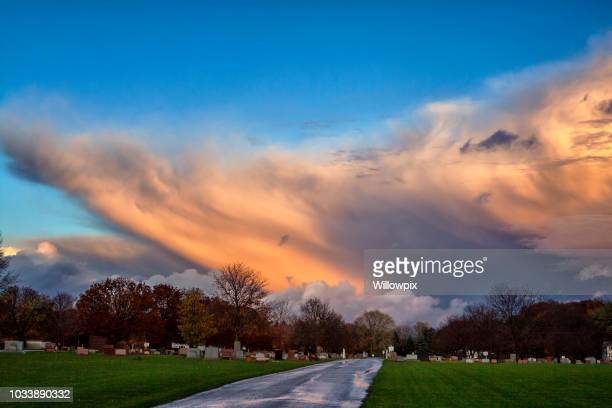 ominous extreme weather hailstorm spooky sunset cemetery cloudscape - extreme weather stock pictures, royalty-free photos & images