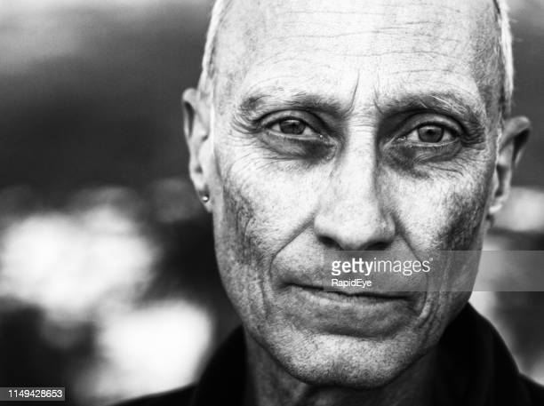 ominous looking senior man stares at camera - atmospheric mood stock pictures, royalty-free photos & images