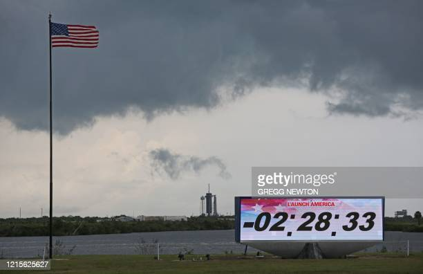 TOPSHOT Ominous weather is seen above launch pad 39A at Cape Canaveral as the countdown clock continues on launch day at the Kennedy Space Center in...