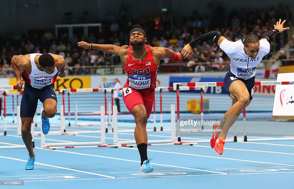 Omo Osaghae of the United States crosses the line to win the gold medal from silver medalist Pascal Martinot-Lagarde of France and William Sharman (L) of Great Britain in the Men's 60m Hurdles Final during day three of the IAAF World Indoor Championships at Ergo Arena on March 9, 2014 in Sopot, Poland.