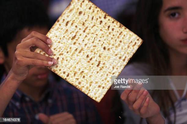 Omri Brandes and Nitzan Brandes eat matzo during a community Passover Seder at Beth Israel synagogue on March 25 2013 in Miami Beach Florida The...