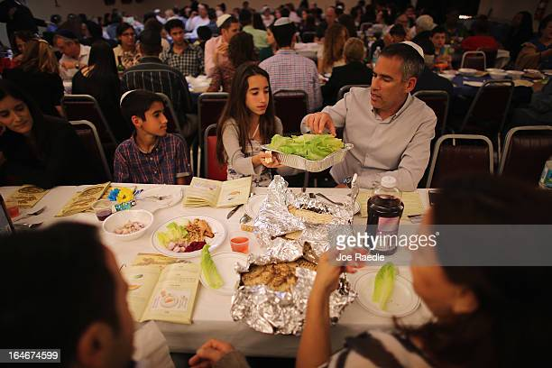 Omri Brandes Nitzan Brandes and Bentsi Brandes eat during a community Passover Seder at Beth Israel synagogue on March 25 2013 in Miami Beach Florida...