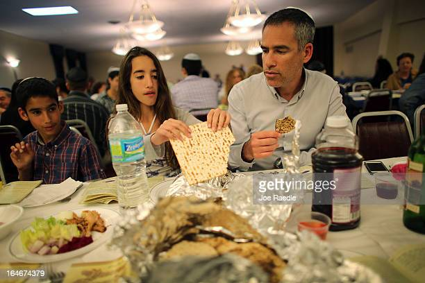Omri Brandes Nitzan Brandes and Bentsi Brandes eat matzo during a community Passover Seder at Beth Israel synagogue on March 25 2013 in Miami Beach...