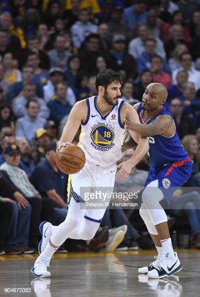 Omri Casspi of the Golden State Warriors dribbles the ball while closely guarded by CJ Williams of the LA Clippers during the first half of their NBA...