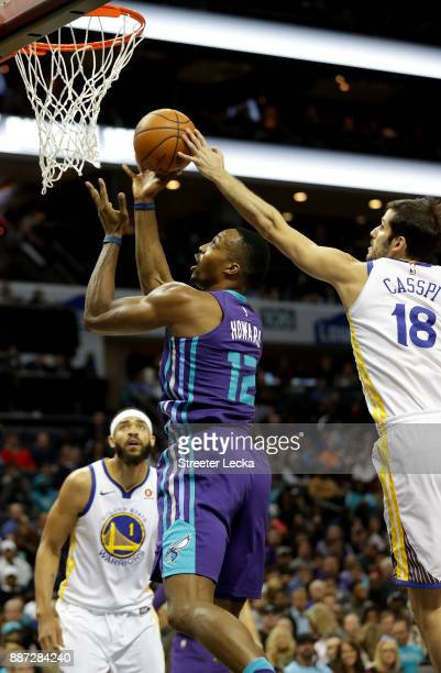 Omri Casspi of the Golden State Warriors tries to stop Dwight Howard of the Charlotte Hornets during their game at Spectrum Center on December 6 2017...