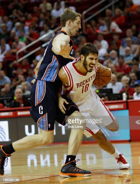 Omri Casspi of the Houston Rockets drives around Cody Zeller of the Charlotte Bobcats at Toyota Center on October 30 2013 in Houston Texas NOTE TO...