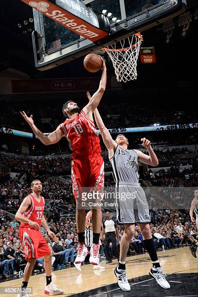 Omri Casspi of the Houston Rockets grabs a rebound against Matt Bonner of the San Antonio Spurs at the ATT Center on November 30 2013 in San Antonio...