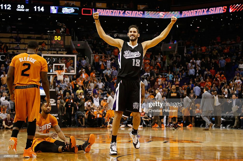 Omri Casspi #18 of the Sacramento Kings celebrates alongside Eric Bledsoe #2 and Marcus Morris #15 of the Phoenix Suns after the Kings defeated the Suns 114-112 in double overtime following the NBA game at US Airways Center on November 7, 2014 in Phoenix, Arizona.