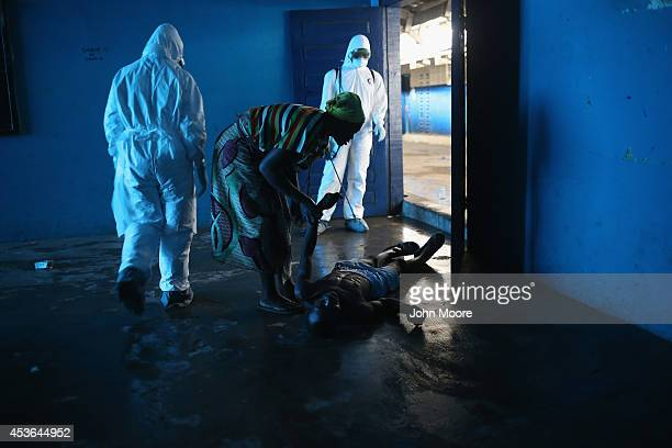 Omu Fahnbulleh tries to help her husband Ibrahim after he fell and was knocked unconscious in an Ebola ward on August 15 2014 in Monrovia Liberia...