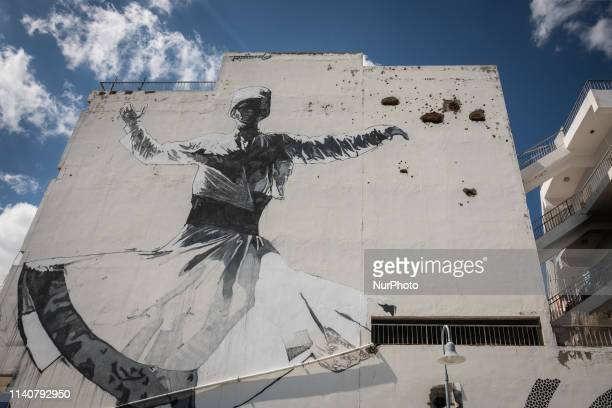 On 22 April 2019, bullet holes and war damage is visible next to graffiti on a building on the green line in north Nicosia, or Lefkosa, the capital...