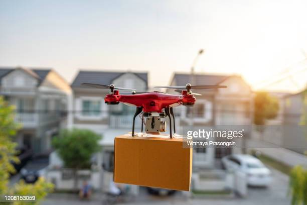 on 23 february 2020, bangkok, thailand delivery drone carrying urgent shipment box in a city. - drone stock pictures, royalty-free photos & images