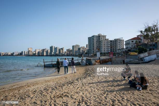 On 24 April 2019, tourists sit on Palm Beach in Famagusta, also known as Gazimagusa, in Northern Cyprus, near a military separation line that blocks...