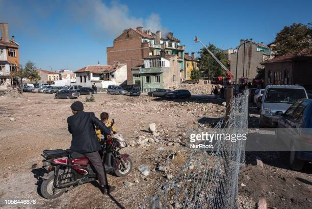 On 27 Oct 2018 a man on a scooter and young boy sit in front of a house fire occurring in abandoned buildings in central Konya an Anatolian city in...
