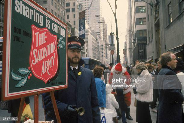 On 5th Avenue a Salvation Army volunteer rings a bell to solicite for charity while in the background an man dressed as Santa Claus greets children...