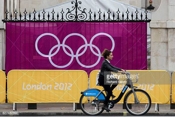 On a Barclays Banksponsored 'Boris' bike a woman cyclist pedals past IOC's Olympic logo brand of rings on a banner at Horse Guards in Whitehall...