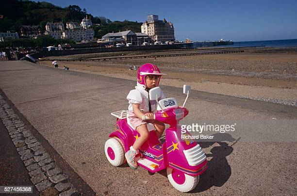 On a bright summer afternoon a young spoiled girl showsoff by riding her favourite motorized Barbie trike along The Parade the main promenade in the...