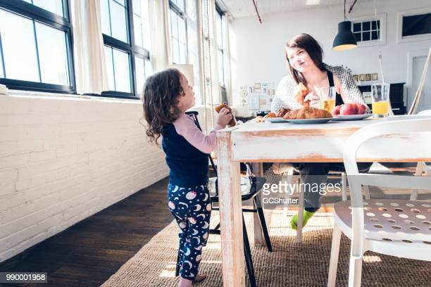 On a bright summer morning, mother and daughter enjoying their breakfast at home