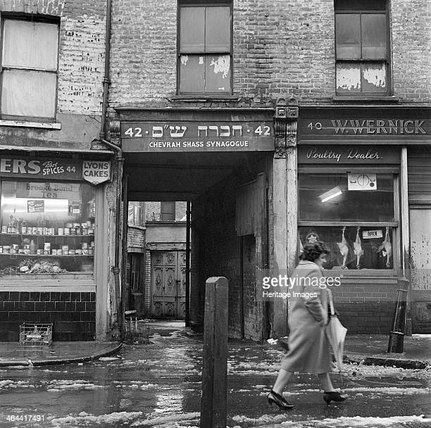 On a cold day a woman walks past the Chevrah Shass Synagogue which is tucked away down an alley Whitechapel Stepney London c1946c1959 The carriage...