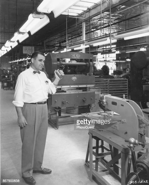 On a factory floor an unidentified man holds up a Motorolabrand HandieTalkie Radio Pager Chicago Illinois 1956
