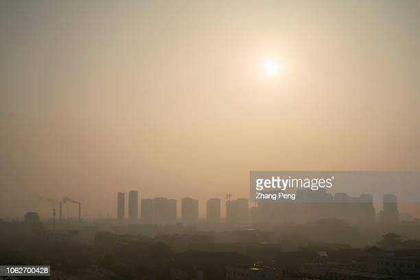 On a hazy morning chimney of chemistry factory emits smoke to sky at the suburb surrounding the residential district Entering Winter the northern...