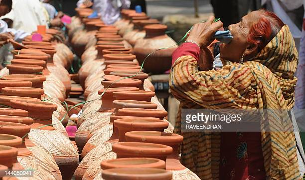 On a hot summer day a woman drinks water stored in clay pots on the streets of New Delhi on May 9 2012 Heat wave conditions prevailed in the city and...